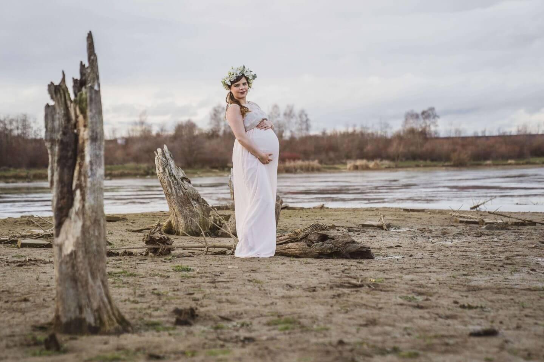 schwangere Frau in weißem Kleid am Strand