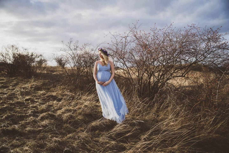 Schwangere in blauem Tüllkleid vor dramatischem Himmel