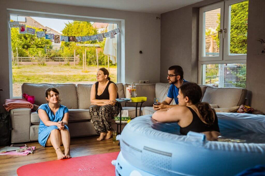 Mutter sitzt im Wohnzimmer im ausgeblasenen, blauen Geburtspool, begleitet durch Hebamme, Doula und Partner