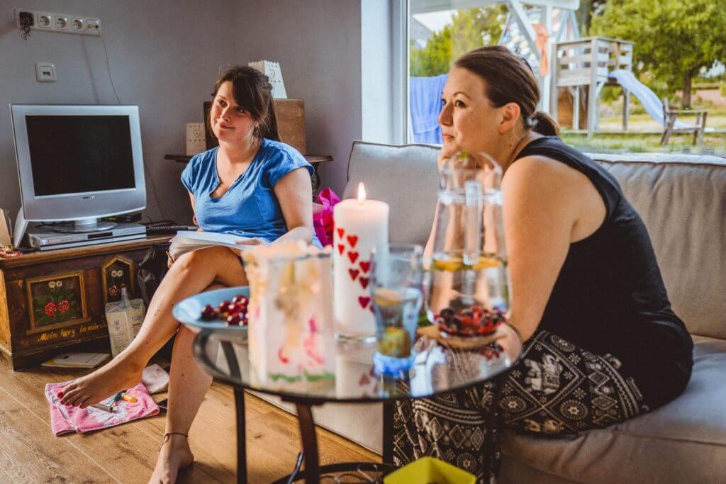 Hebamme Michelle und Doula Seli sitzen auf der Couch, im Vordergrund Kerzen und Früchte