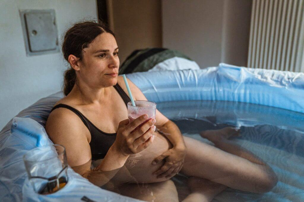 Mutter sitzt im aufblasbaren Geburtspool und trinkt einen rosanen Smoothie