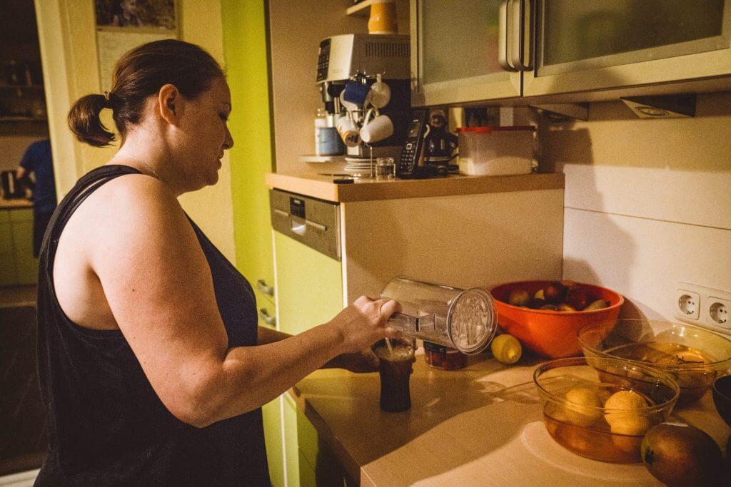 Frau steht in Küche und bereitet einen Smoothie zu