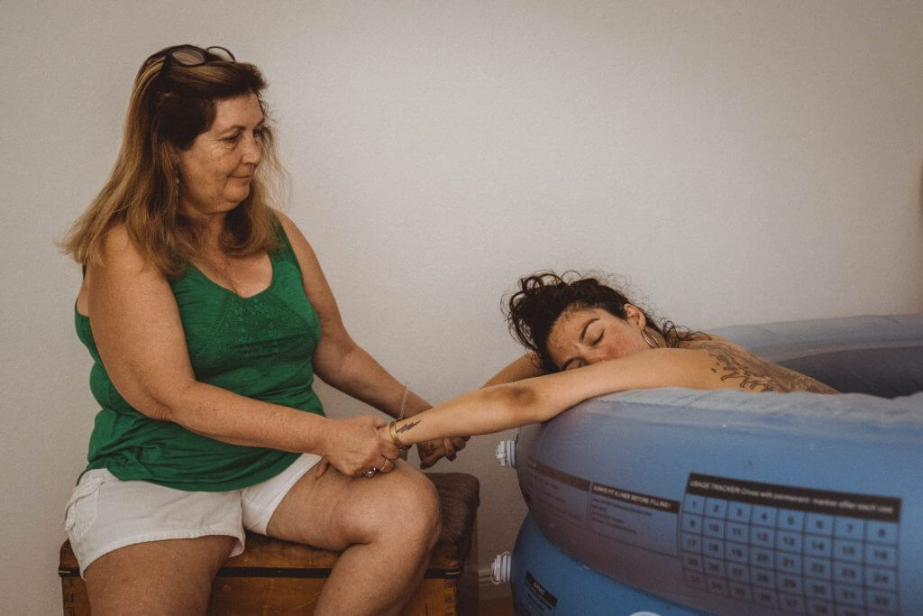 Mutter hält ihrer gebärenden Tochter die Hände