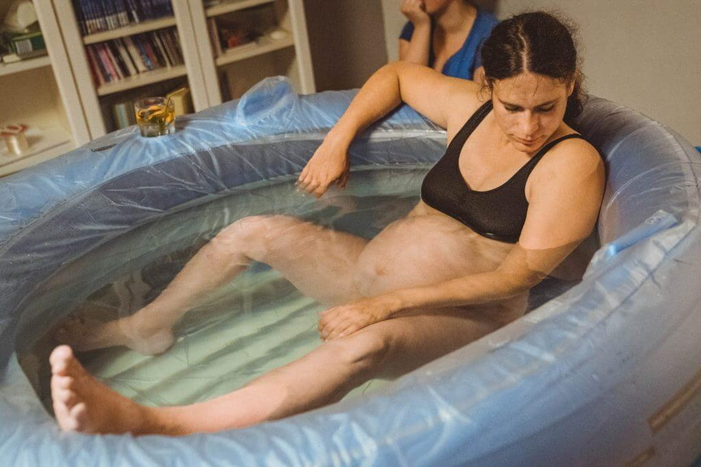 Frau sitzt in Geburtspool