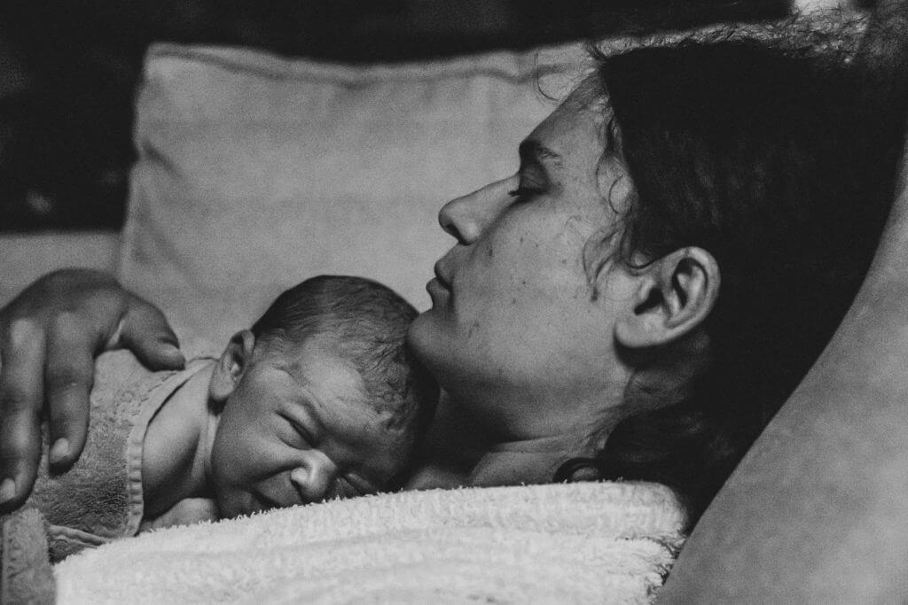 Mama kuschelt Neugeborenes