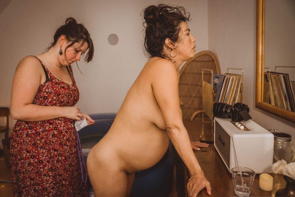 Hebamme klebt Tens-Gerät auf Mutter während der Geburt