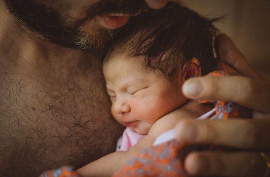 Neugeborenes wird von Papa gehalten