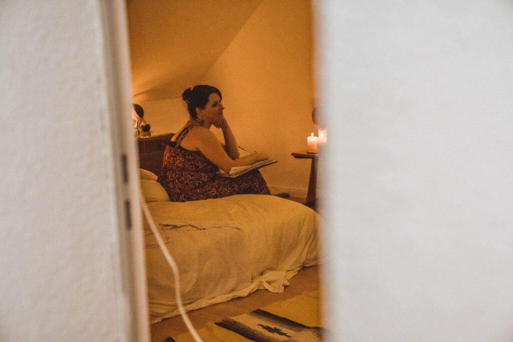 Blick durch die Tür, Hebamme sitzt beobachtend auf dem Bett