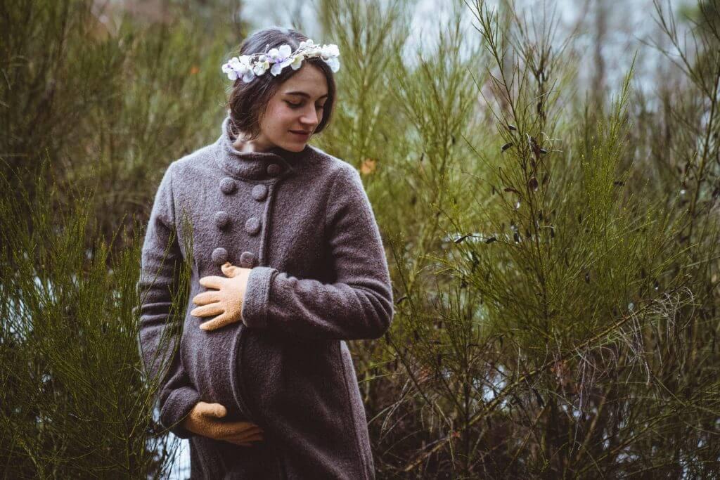 Schwangere hält Babybauch vor winterlichen Büschen