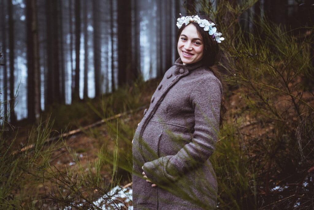 Schwangere lacht in Kamera und hält Babybauch