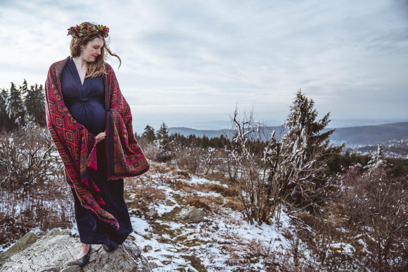 Schwangere steht auf Fels im Wind