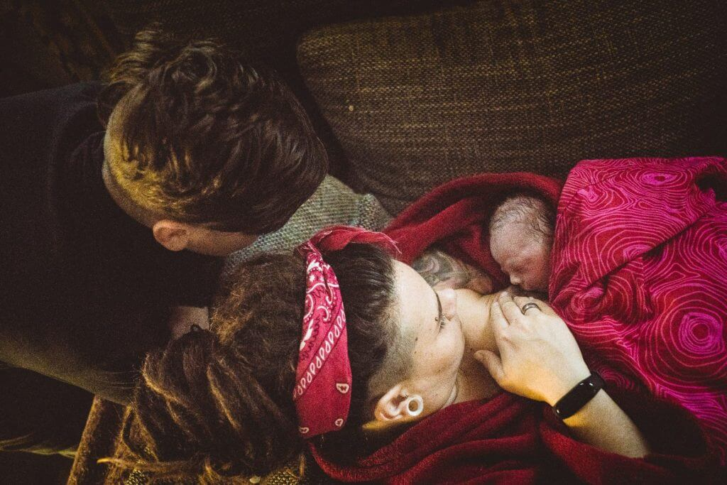 Bruder inspiziert Neugeborenes nach Hausgeburt auf der Couch