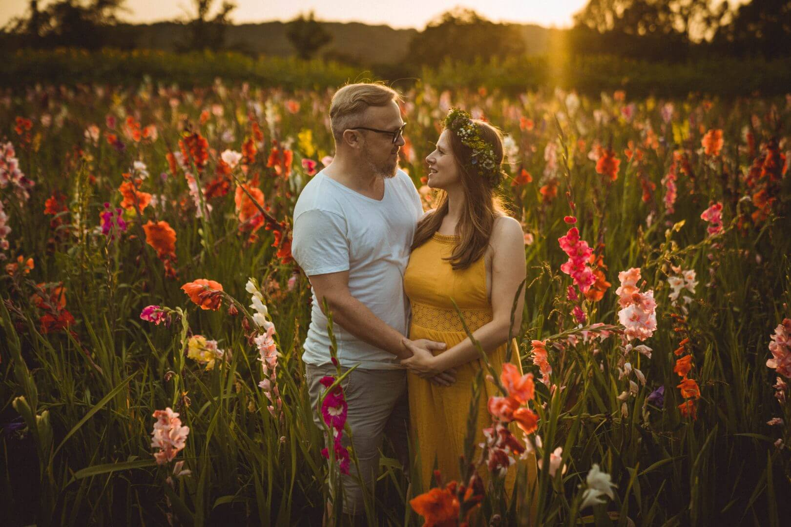 Paar steht in Gladiolenfeld im Sonnenuntergang