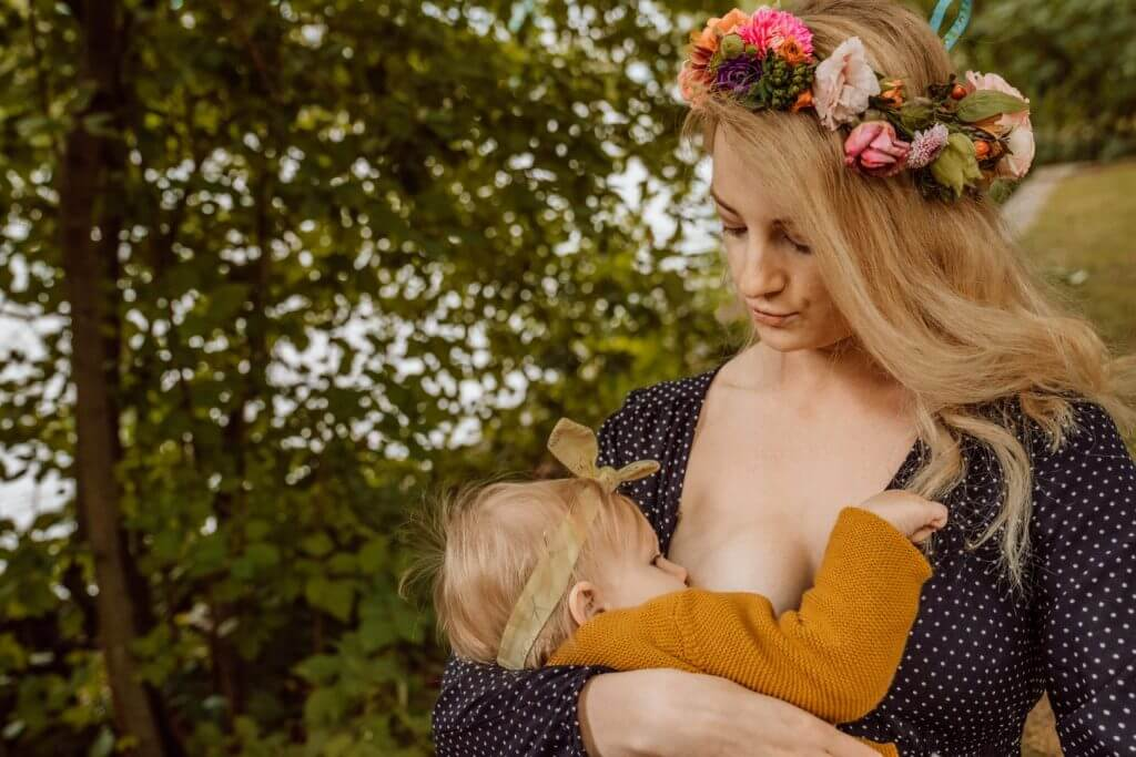 Mutter mit Blumenkranz stillt Baby mit Stirnband