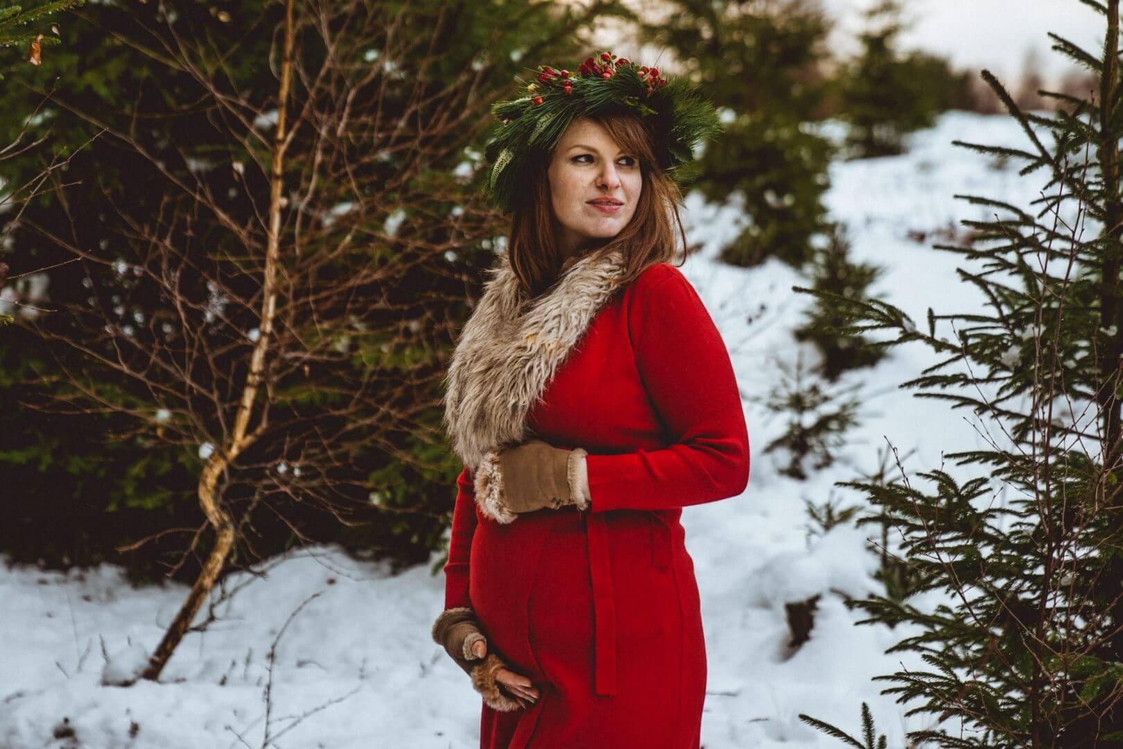 Schwangere hält Babybauch mit Handschuhen in rotem Kleid