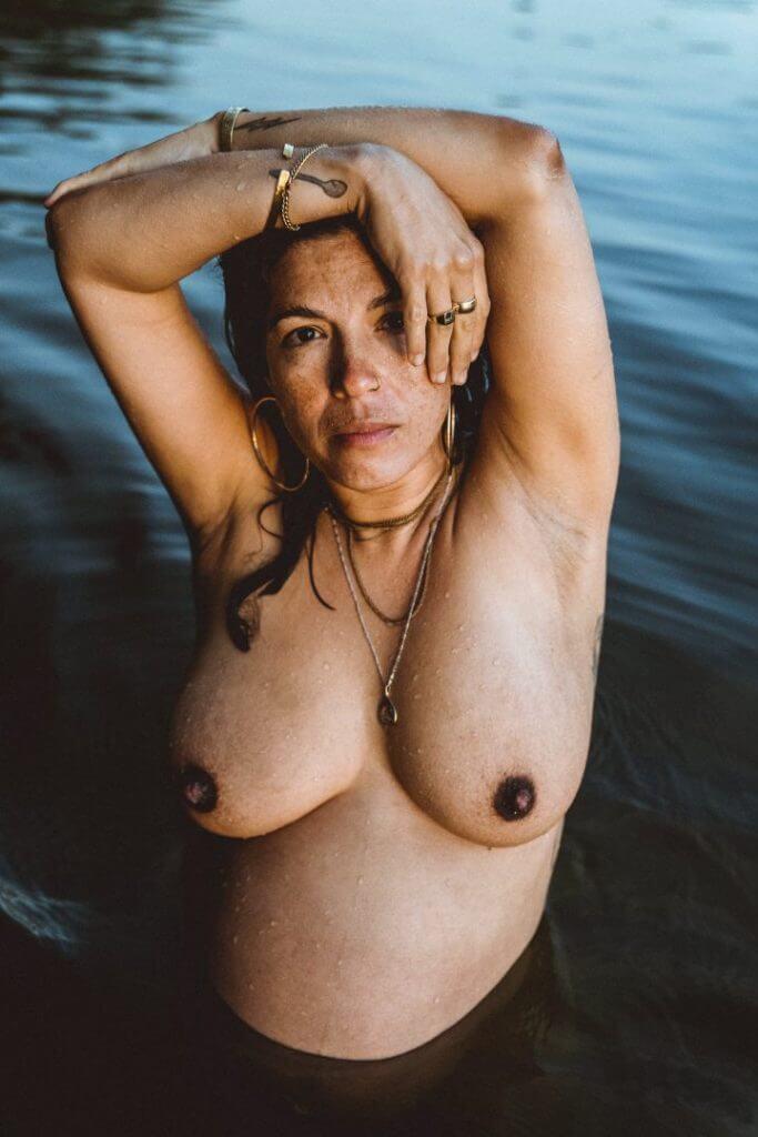 Schwangere hält Hände über Kopf im Wasser
