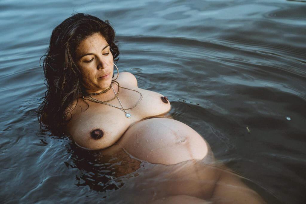 Schwangere treibt im Wasser während des Sonnenuntergangs