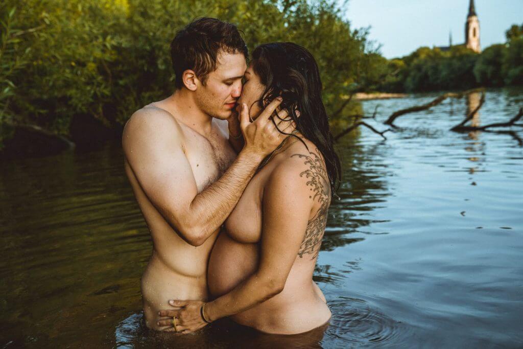 Paar küsst sich im Wasser, im Hintergrund Büsche und ein Kirchenturm