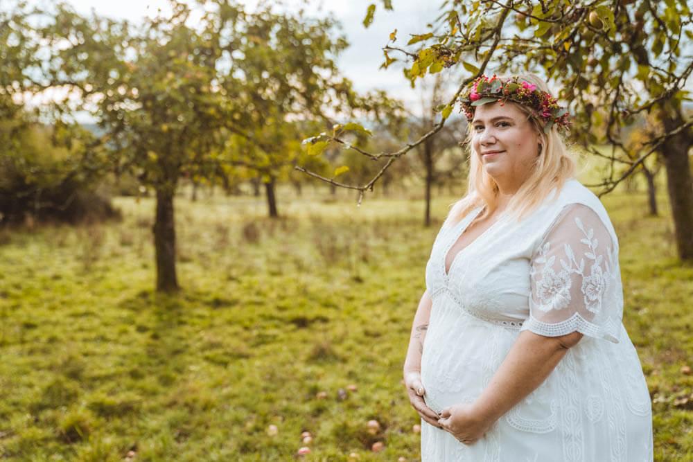 Plus-Size-Schwangere hält Babybauch in weißem Kleid unter Apfelbaum