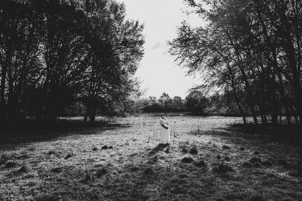 Schwangere in weißem Kleid steht auf Waldlichtung