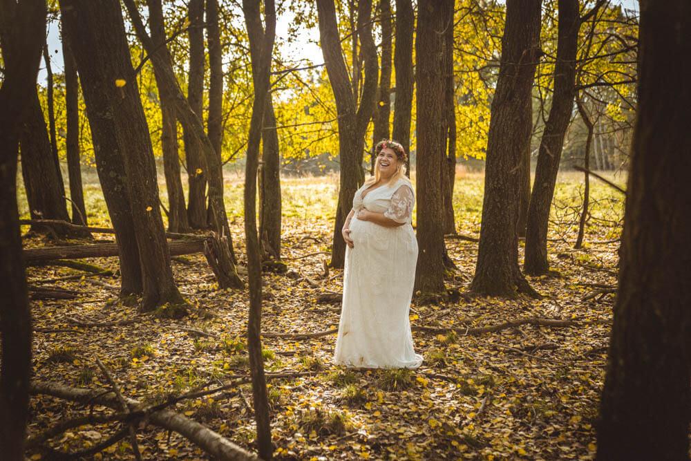 Schwangere in weißem Kleid steht in Baumgruppe im Blätterregen