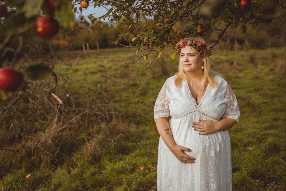 Schwangere streichelt Babybauch unter Apfelbaum