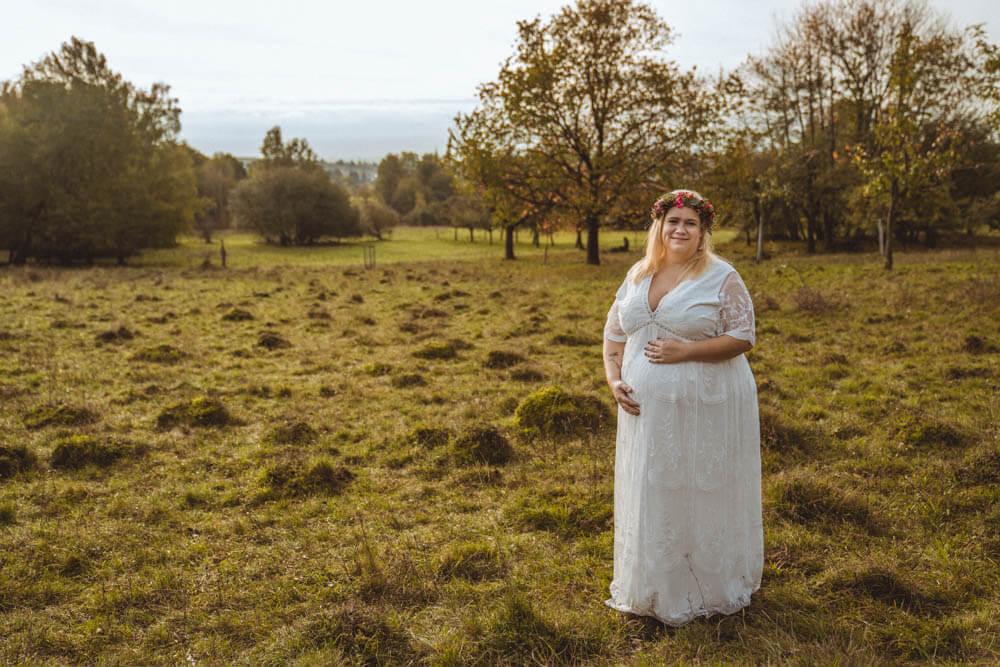 Schwangere in weißem Kleid steht auf Streuobstwiese