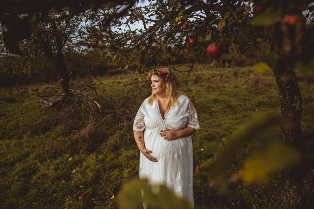 Schwangere in weißem Kleid steht unter Apfelbaum