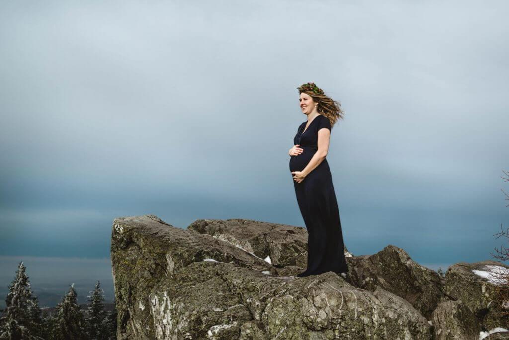 Schwangere in blauem Kleid steht auf Felsen