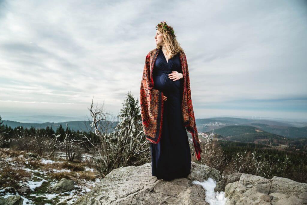 Schwangere in blauem Kleid mit rotem Cardigan steht auf Felsen