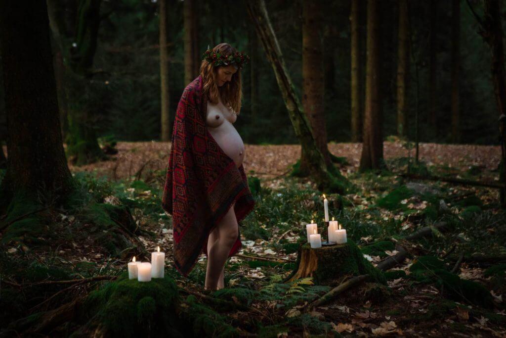 Schwangere steht umringt von Kerzen im Wald und hält rotes Tuch