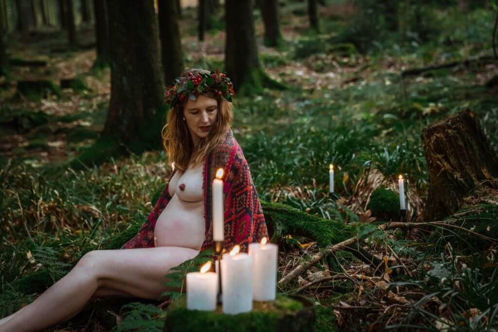 Schwangere sitzt mit Kerzen im Wald