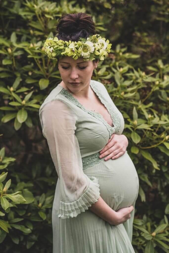 Schwangere mit Blumenkrone steht vor Busch und hält Babybauch