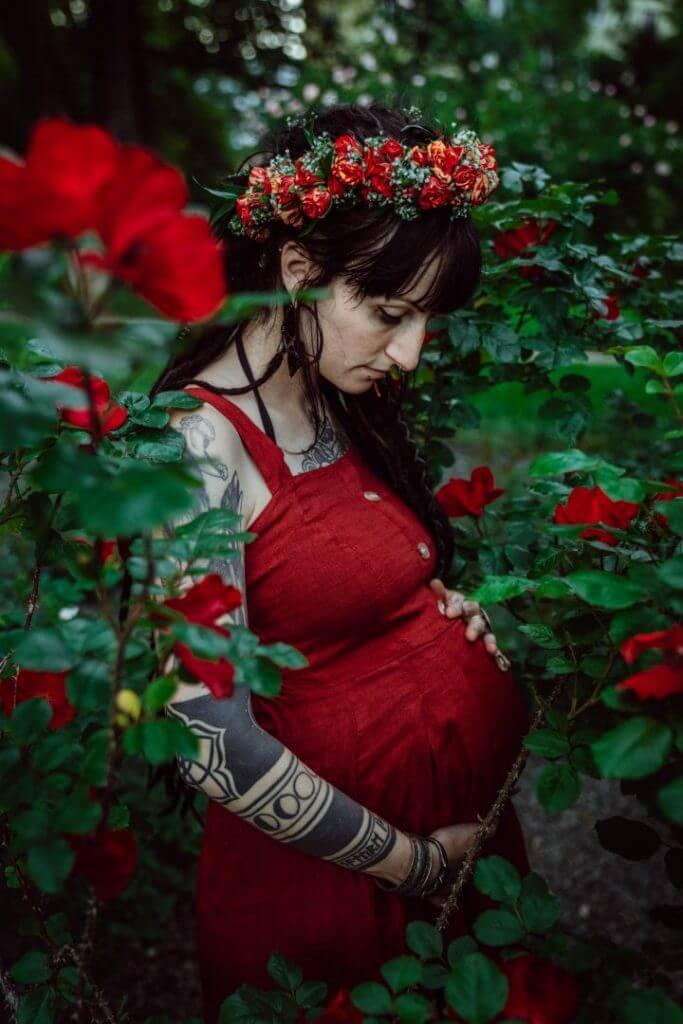 Schwangere hält Babybauch vor Rosen
