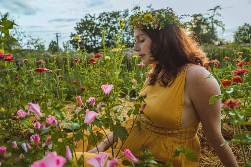 Schwangere sitzt in rosa Blumenfeld und blickt auf Babybauch