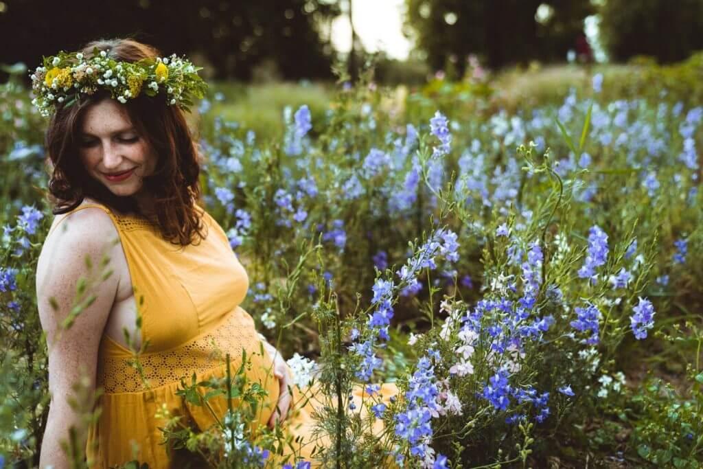 Schwangere in gelbem Kleid sitzt in blauen Blumenfeld und hält Babybauch