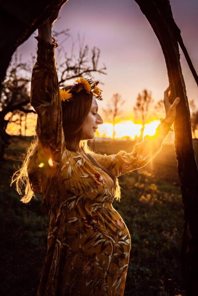 Schwangere im Sonnenuntergang zwischen Baumästen