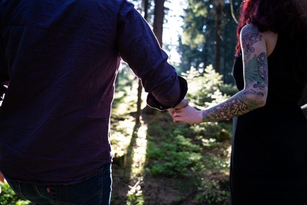 Paar mit tattowierten Armen halten Händchen im Sonnenuntergang