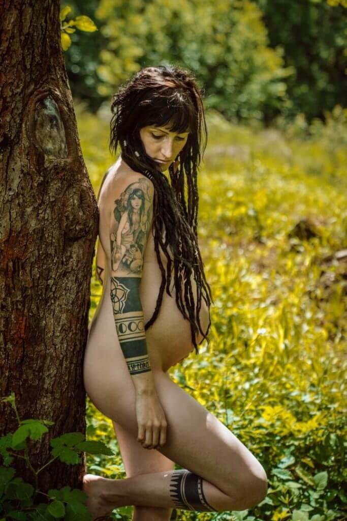 Schwangere mit Dreadlocks und Tattoos lehnt an Baum