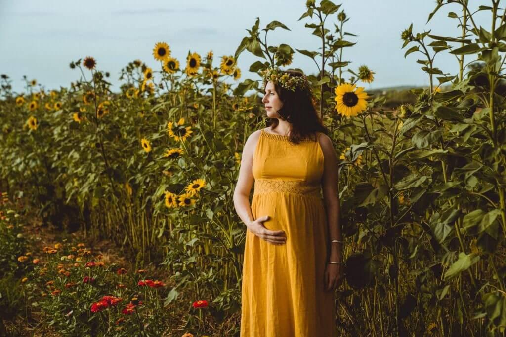 Schwangere steht vor Sonnenblumenfeld und hält Bauch