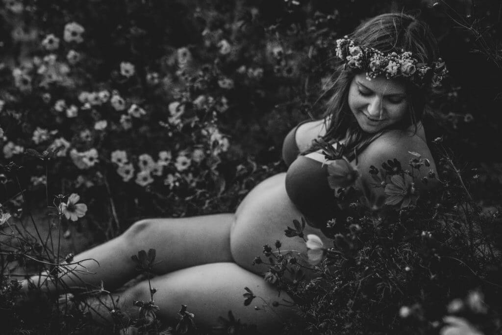 Schwangere sitzt in Unterwäsche in Blumenfeld