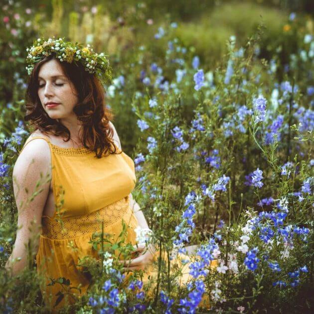 Schwangere sitzt in blauem Blumenfeld