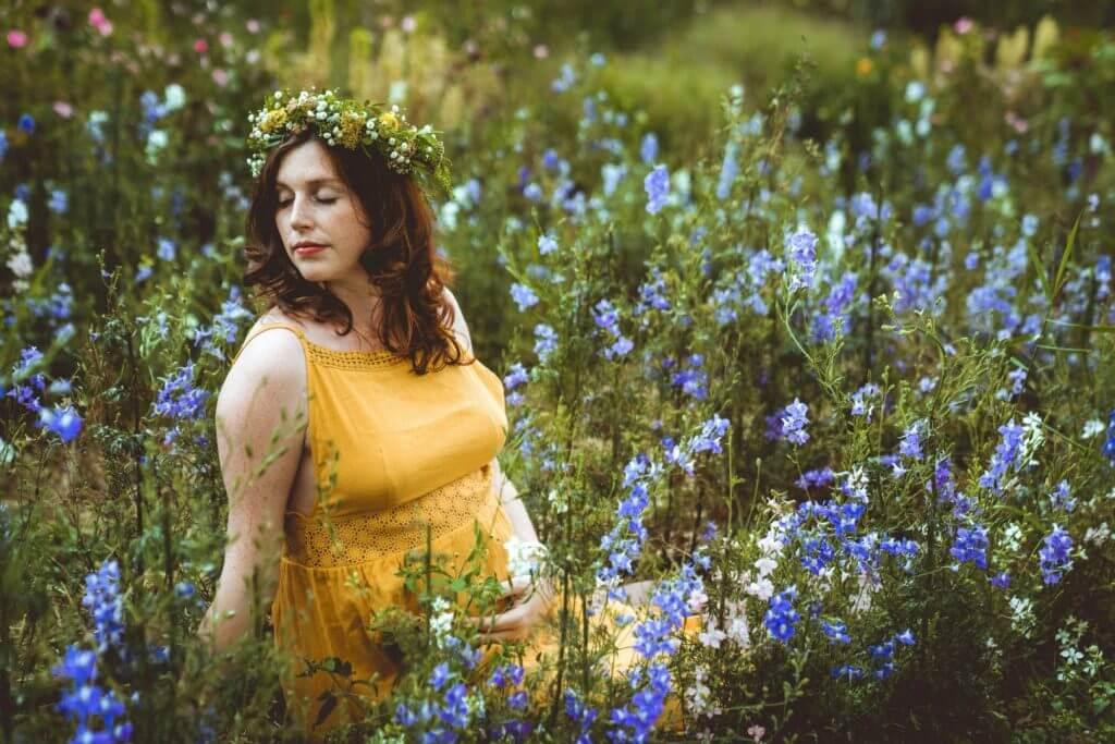 Schwangere mit Blütenkranz und gelbem Kleid sitzt in blauen Blüten