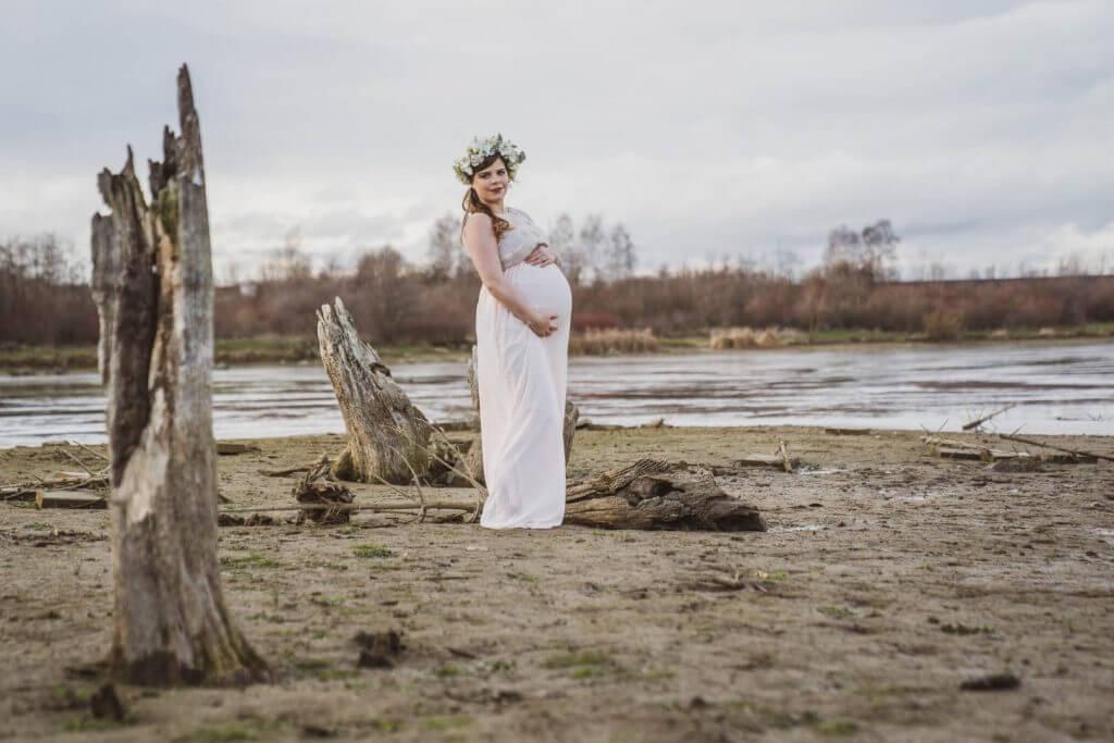Schwangere steht am Wasser und hält Babybauch