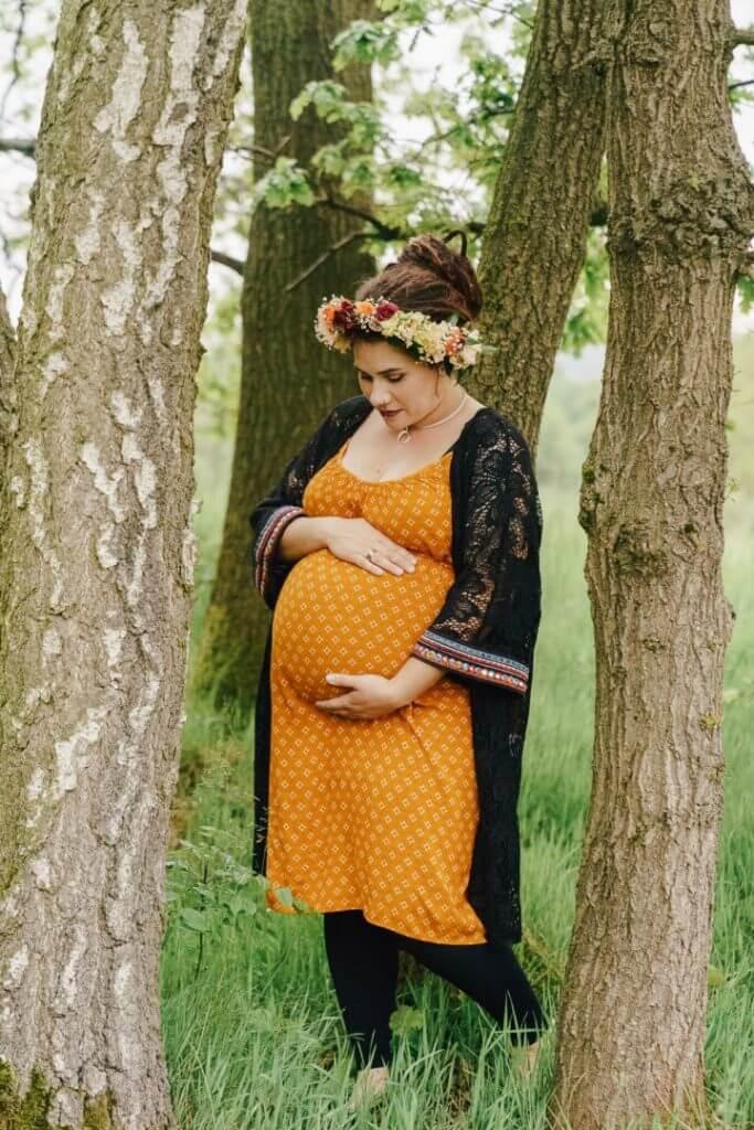 Schwangere steht in Baumgruppen und hält ihren Bauch