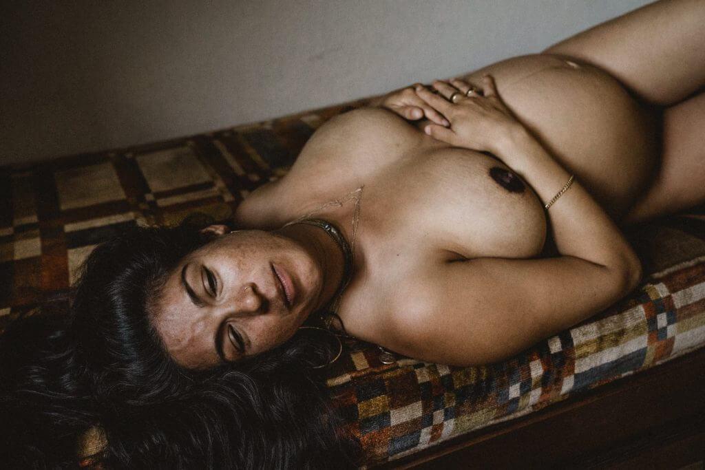 Schwangere liegt auf Sofa und hält Hände auf Bauch