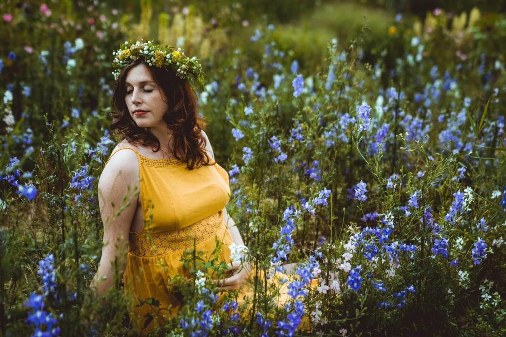 Schwangere in orangenem Kleid in blauem Blumenfeld