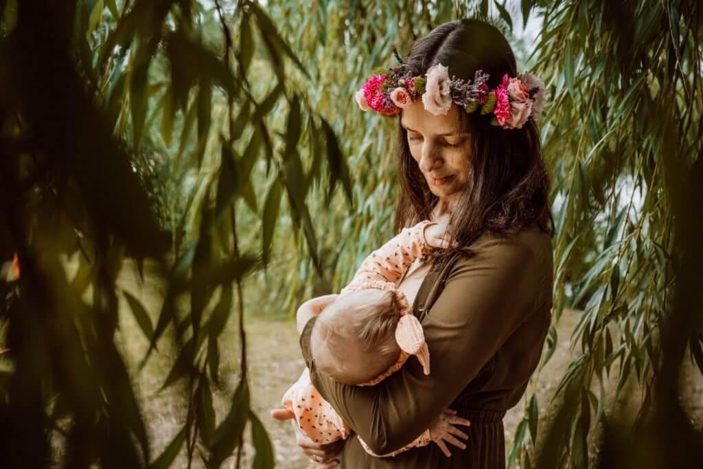 Mutter mit Blumenkranz stillt Baby unter Trauerweide