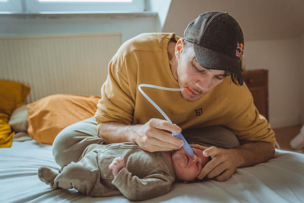 Papa saugt Baby Nasensekret ab
