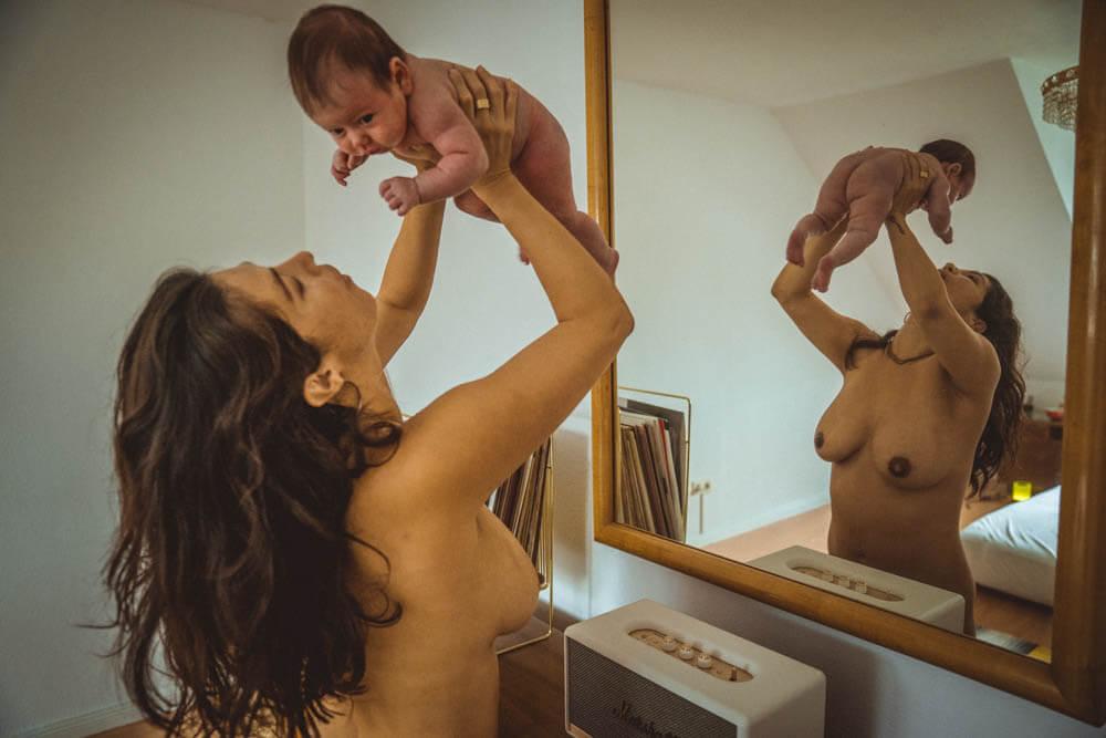 Mutter hält Baby vor Spiegel hoch
